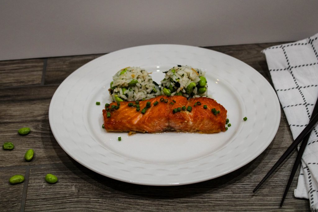 miso glazed salmon on a white plate with edamame rice