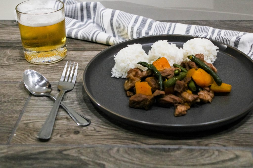 pork, squash green beans, and rice on a gray plate with a fork and spoon and glass of beer