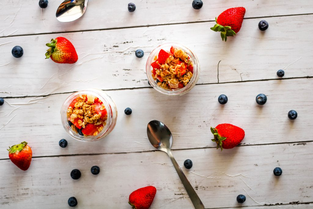 top down view of yogurt parfait with granola, strawberries, and blueberries