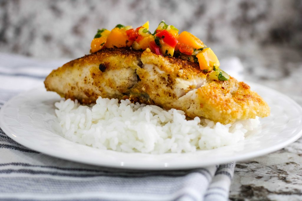 side view of fish with mango salsa on white rice