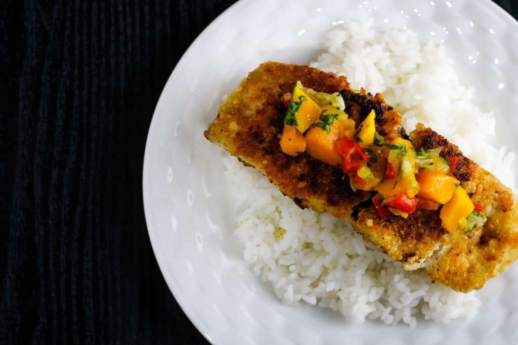 top down view of fish on white rice with mango salsa