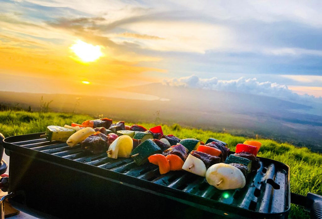 venison kabobs on a grill with a sunset backdrop