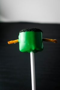 marshmallow on a stick dipped in green chocolate with black sprinkles on top and pretzels on the side