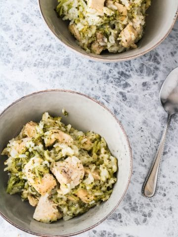 two bowls of chicken broccoli rice with a spoon