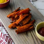 sweet potato fries on a cutting board with ketchup and mustard