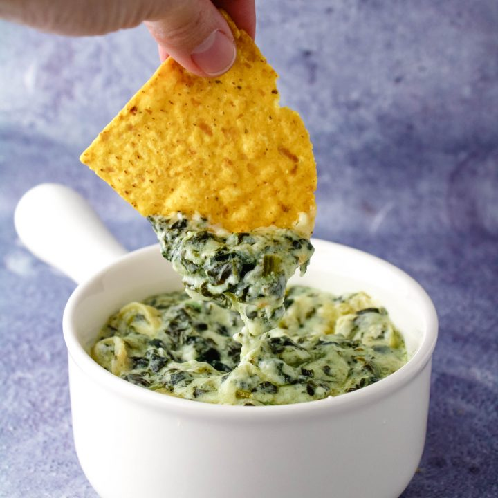 hand dipping a chip in spinach artichoke dip