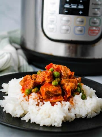instant pot pork and peas on a black place with rice