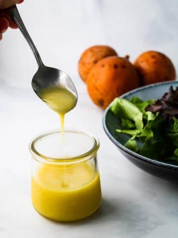lilikoi vinaigrette dripping off a spoon into a glass jar