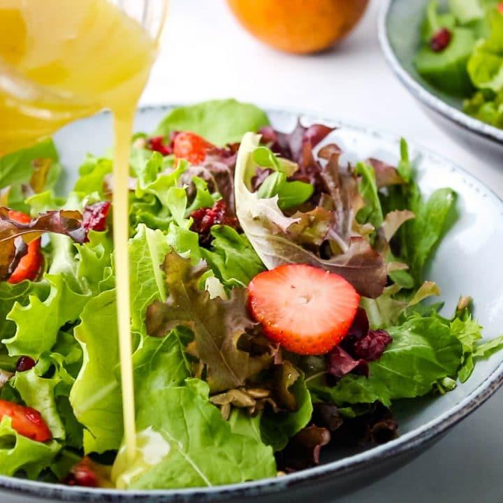 pouring lilikoi vinaigrette over a spring salad