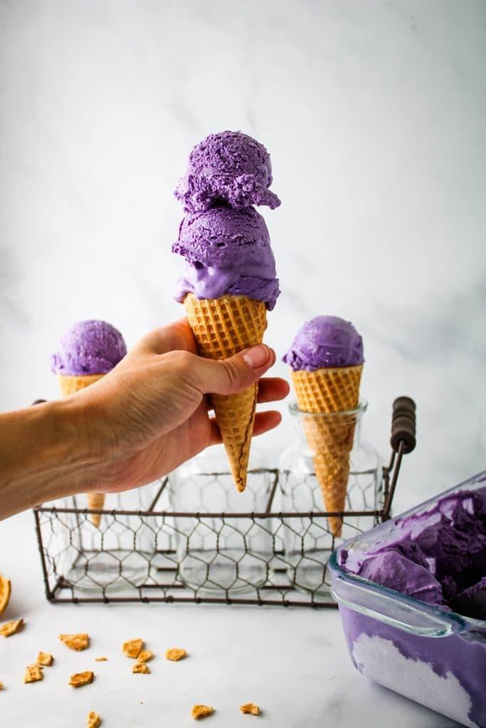 3 ube ice cream scoops on a sugar cone
