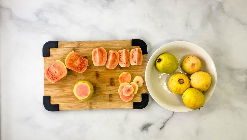 cut guavas on a cutting board for guava jam