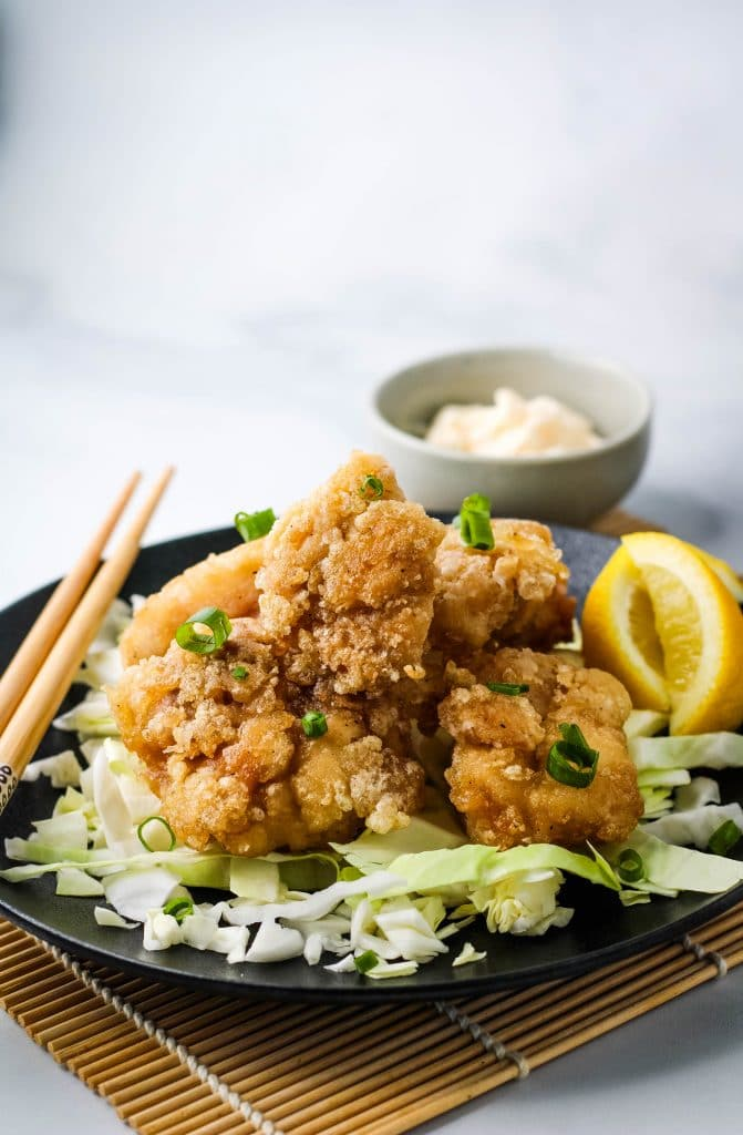 chicken karaage on a bed of shredded cabbage on a black plate