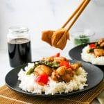 hand using chopsticks to pick up teriyaki chicken stir fry