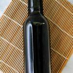 Homemade teriyaki sauce in a glass bottle on a babmoo mat