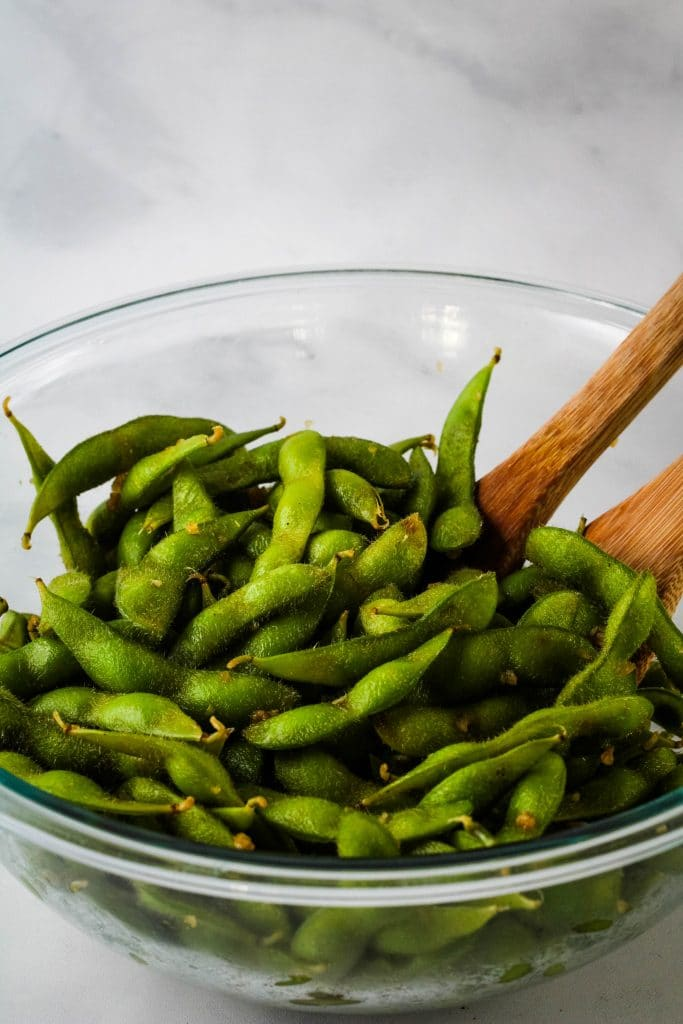 edamame in a glass bowl with wooden spoons
