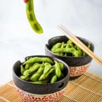 hand picking up edamame from a black bowl