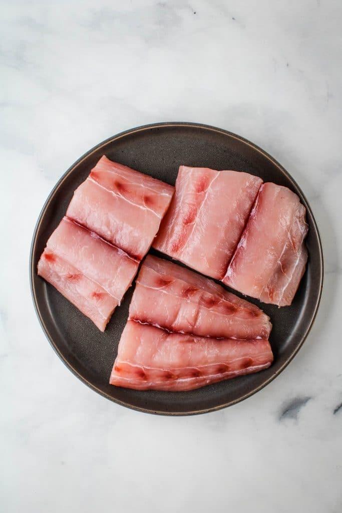 fresh mahimahi on a black plate