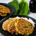 tuna patties and rice on a black plate
