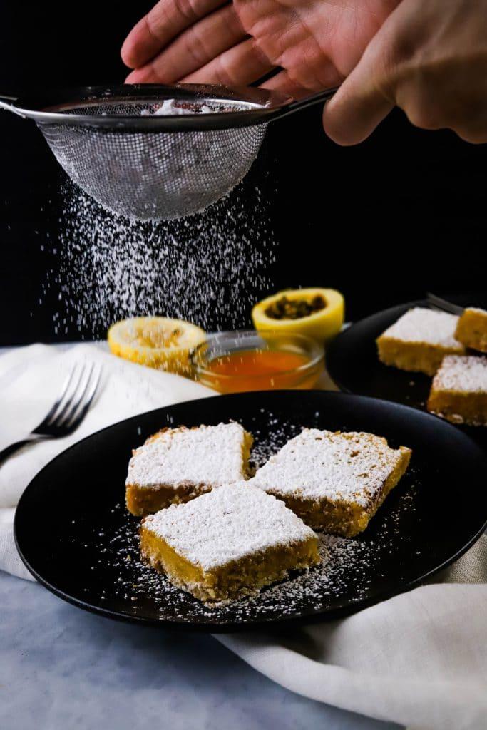 sprinkling powered sugar on lilikoi bars
