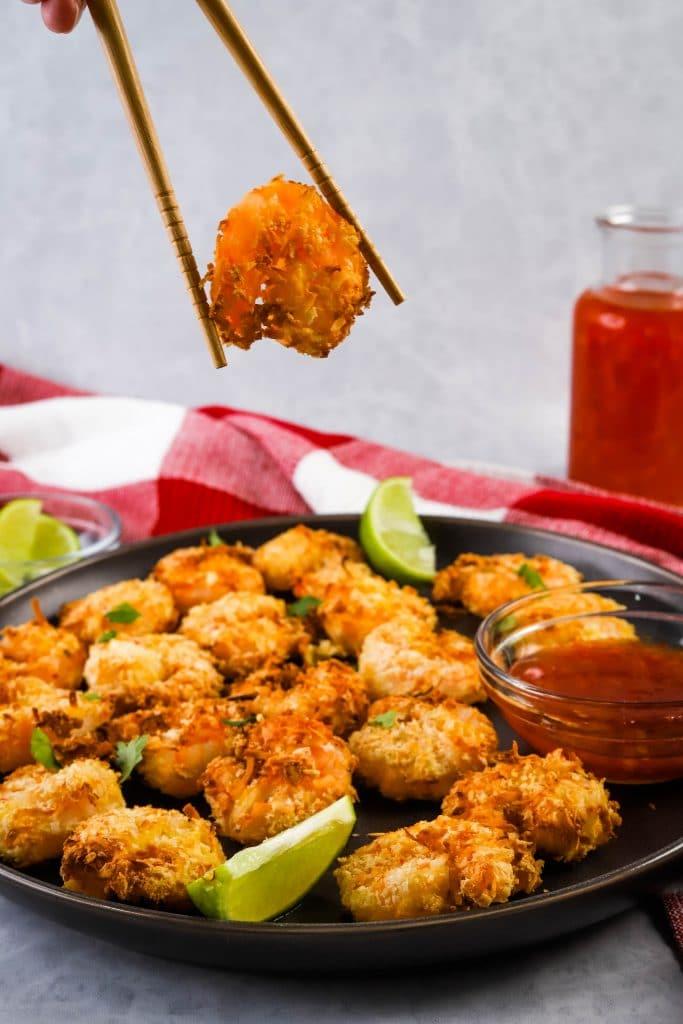 chopsticks picking up air fryer coconut shrimp