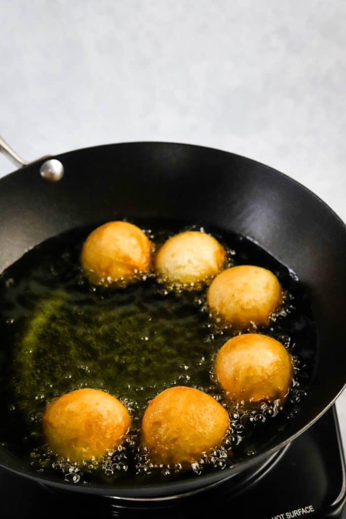 andagi frying in a wok