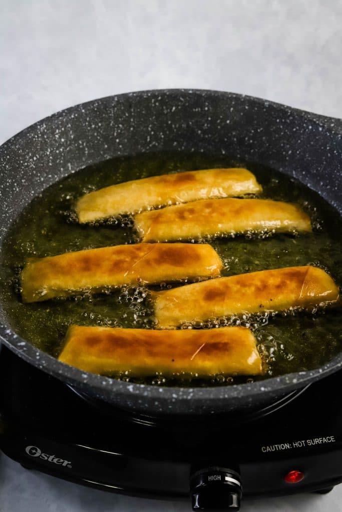 banana lumpia in a frying pan