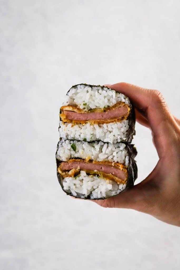 hand holding a spam katsu musubi cut in half