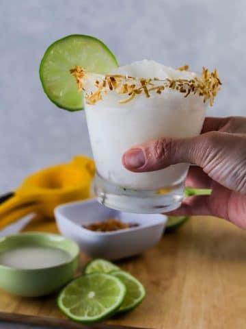 hand hodling a frozen coconut margarita
