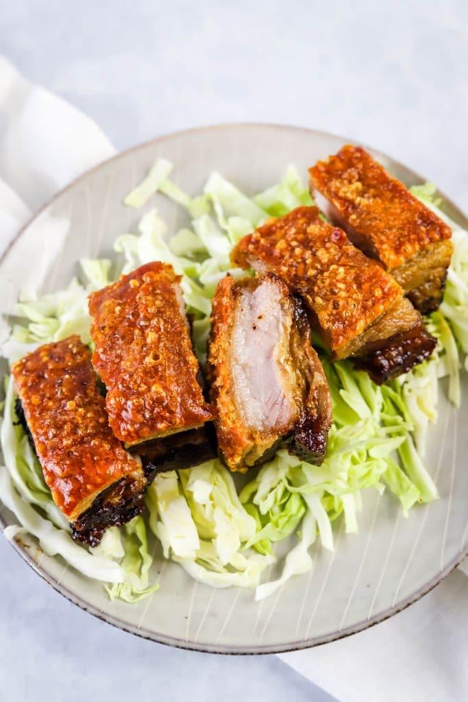 crispy pork belly on a bed of shredded cabbage